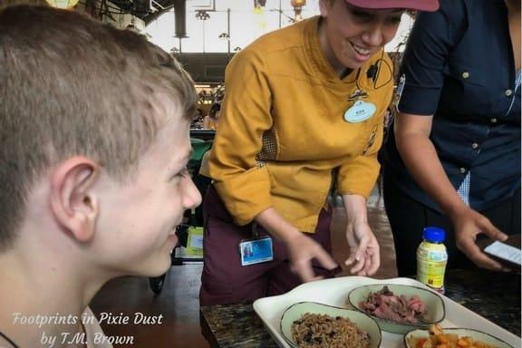 Disney Cast Member delivering food allergy safe meal at Satu'li Canteen at Disney's Animal Kingdom