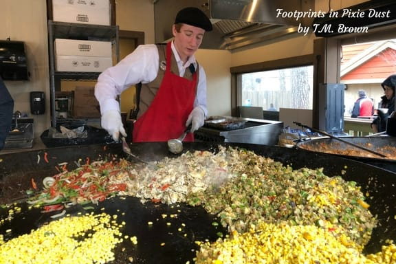 Young man cooking up a skillet meal in a six foot iron skillet at Silver Dollar City