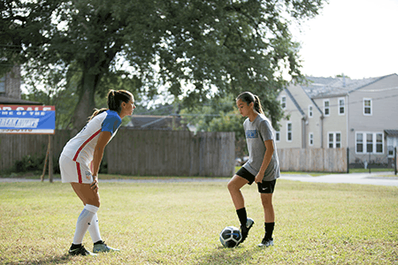 Siena Agudong as Reagan and Alex Morgan, soccer superstar, in Alex & Me