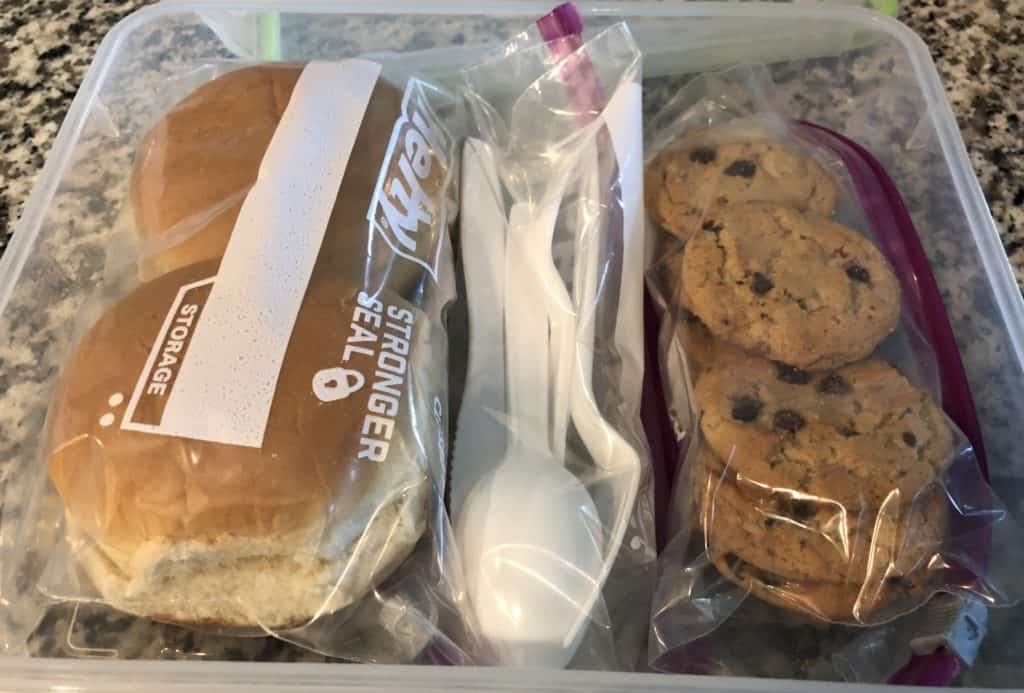 container with buns, plastic ware and cookies